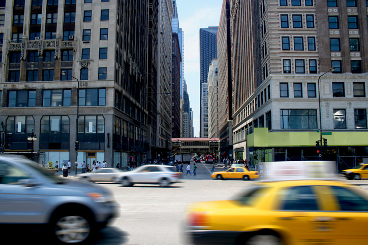 Cars race by on a busy Chicago street