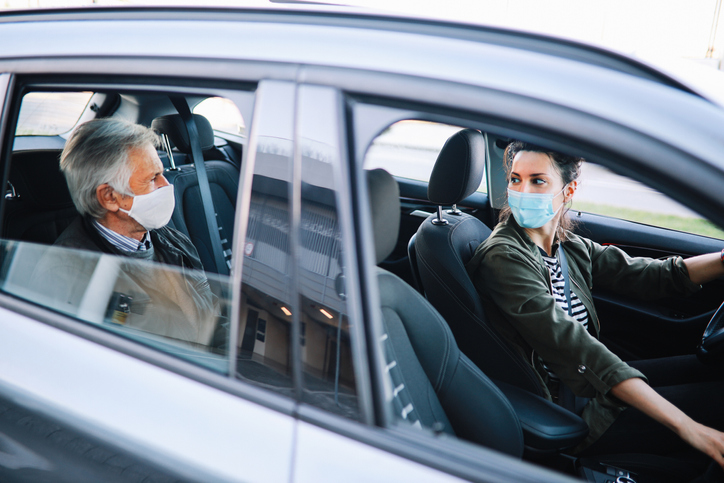 A rideshare driver and passenger wear protective face masks to prevent COVID-19 spread.